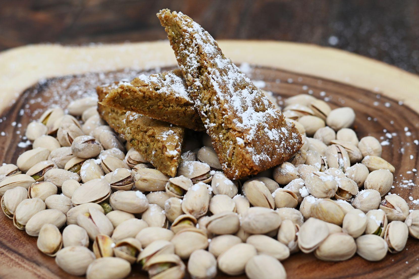 Pistachio shortbread wedges served on a pile of pistachios