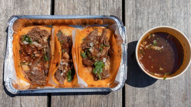 An overhead view of three beef birria tacos in an aluminum takeaway container with a consomme soup on the side. Istockimage downloaded for TikTok recipes and food trends feature.GoodFoodApril 2021.