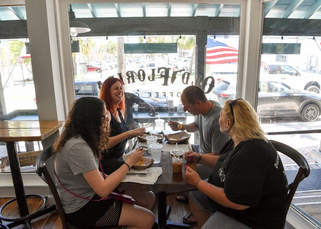"""The Metz family, Zoe (front left), 16, Shelly (back left), Stephen (back right), of Columbus, Ohio, enjoy their Old Florida crepes with tour guide Debbi Goodman Venturina, of Treasure Coast Culinary Tours, during a walking restaurant tour on Wednesday, June 9, 2021, at Old Florida Coffee in downtown Fort Pierce. The group also visited Cobb's Landing, Taco Dive, Pierced Ciderworks and Pickled Restaurant and Bar. """"What we want to do is give everyone a taste at these restaurants so when they're in the area, they come back,"""" said Venturina. """"That's the whole goal, to support the local businesses."""""""
