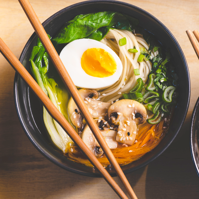 traditional japanese ramen soup with  mushrooms, bok choy, greens in  two black bowls on the orange background, top view, close up