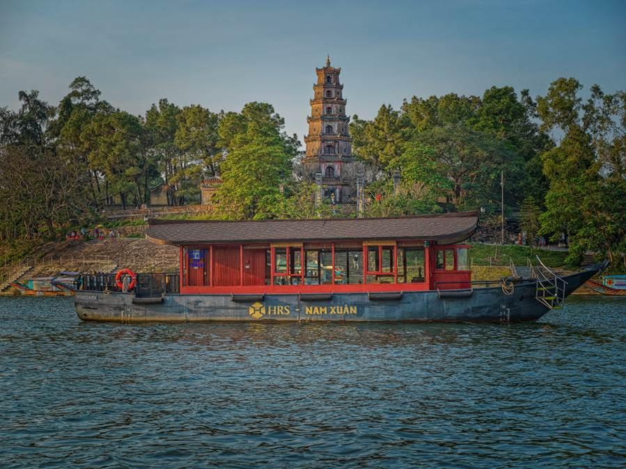 A river cruise tour along the Perfume River through Thien Mu Pagoda, a popular tourist destination in Hue. Photo courtesy of Azerai La Residence.
