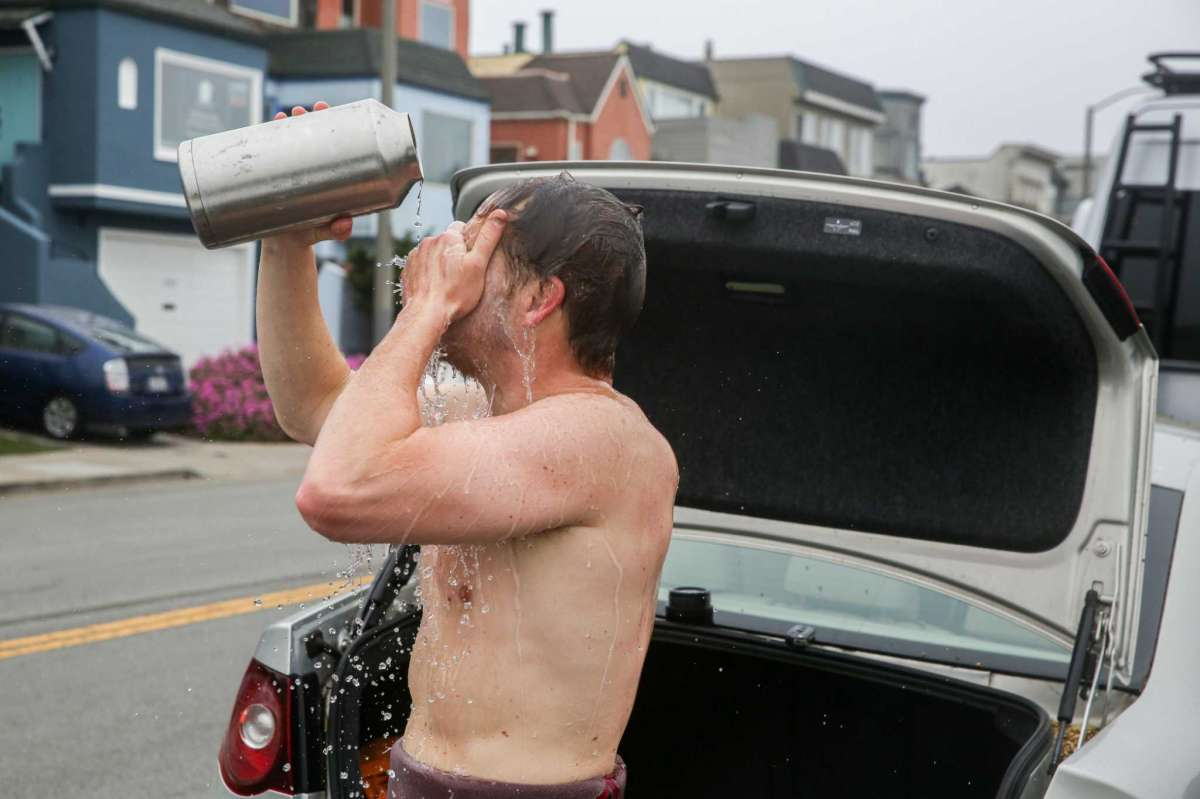 Peterson Harter washes his face after surfing at Ocean Beach in San Francisco. He recently closed his sandwich pop-up for a break to take care of his mental health, and finds relief in surfing.