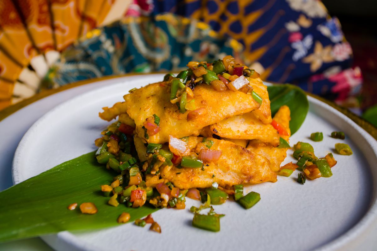 Yellowish, breaded pieces of friend young coconut meat on a white plate with chiles